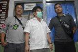 Tersangka kasus korupsi alat kesehatan (alkes) Hari Liewarnata alias Apin (tengah) digiring dua petugas Kejaksaan Negeri (Kejari) Sanggau saat tiba di Lapas Klas IIA Pontianak di Kabupaten Kubu Raya, Kalimantan Barat, Rabu (6/2/2019). Hari Liewarnata yang masuk dalam Daftar Pencarian Orang (DPO) terkait kasus korupsi alkes RSUD Sanggau tahun 2014 tersebut ditangkap Tim Eksekusi Kejari Sanggau dan Adhyaksa Monitoring Center (AMC) Kejaksaan Agung di kediamannya di Grogol Jakarta Barat pada Rabu (6/2/2019) siang. ANTARA FOTO/Jessica Helena Wuysang