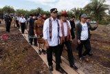 Menteri Perhubungan Budi Karya Sumadi (kiri) bersama Menteri Hukum dan HAM Yasonna Hamonangan Laoly (kedua kiri) berjalan memasuki kawasan lahan pembangunan bandara di Kecamatan Pangmilang, Singkawang Selatan, Kalimantan Barat, Senin (18/2). Pembangunan bandara baru di Kota Singkawang yang akan memiliki landasan pacu ultimate sepanjang 2.500 meter dan mampu menampung pesawat Boeing 737-900 ER tersebut ditargetkan akan selesai pada 2022. ANTARA FOTO/David/jhw