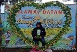 Seorang mahasiswa Al-Azhar Jakarta sedang berfoto dengan latarbelakang banner selamat datang di objek wisata 'Taman Bunga Matahari' di Kampung Rawa Keladi, RT 002 RW 02, Desa Sukamurni, Kecamatan Sukakarya, Kabupaten Bekasi, Jawa Barat. (Megapolitan.antaranews.com/Foto: Pradita Kurniawan Syah).