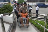 Seorang petugas mendorong kursi roda Pekerja Migran Indonesia (PMI) yang mengalami patah kaki saat Ia tiba di Pos Lintas Batas Negara (PLBN) Entikong, Kabupaten Sanggau, Kalbar, Rabu (27/2/2019). Pemerintah Malaysia mendeportasi 101 PMI (68 pria dan 33 wanita) beserta 10 anak melalui Depot Imigresen Semunja dan Bekenu (Miri) karena tidak memiliki dokumen resmi. Dua PMI di antaranya mengalami patah kaki akibat kecelakaan kerja dan gangguan jiwa. ANTARA FOTO/Agus Alfian/jhw