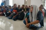 Sejumlah Pekerja Migran Indonesia (PMI) yang dideportasi Pemerintah Malaysia berbaris saat tiba di Pos Lintas Batas Negara (PLBN) Entikong, Kabupaten Sanggau, Kalbar, Rabu (27/2/2019). Pemerintah Malaysia mendeportasi 101 PMI (68 pria dan 33 wanita) beserta 10 anak melalui Depot Imigresen Semunja dan Bekenu (Miri) karena tidak memiliki dokumen resmi. Dua PMI di antaranya mengalami patah kaki akibat kecelakaan kerja dan gangguan jiwa. ANTARA FOTO/Agus Alfian/jhw
