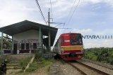 Kereta api Commuter line melintas di samping stasiun Pondok Rajeg yang terbengkalai, Cibinong , Bogor, Jawa Barat, Sabtu (2/2/2019). Stasiun yang sudah tidak beroperasi ini kondisinya sangat memprihatinkan karena sejumlah fasilitas yang ada di stasiun ini terlihat rusak dan dipenuhi coretan di dindingnya. ANTARA JABAR/Yulius Satria Wijaya/agr.