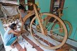 Perajin kayu Sarijo (kanan) bersama anaknya mencoba sepeda kayu buatannya, di Seworagan, Tambakan, Jogonalan, Klaten, Jawa Tengah, Minggu (3/3/219). Sepeda kayu yang memanfaatkan limbah kayu nangka, waru dan mindi itu dijual dengan harga Rp 10 juta - Rp 15 juta tergantung ukuran. (ANTARA FOTO)