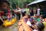 Kapolres Bojonegoro AKPB Ary Fadli (tengah) membobong bayidalam evakuasi sejumlah warga korban banjir di Desa Sukorejo, Kecamatan Kota, Rabu (6/3). Dalam proses evakuasi dengan memanfaatkan perahu karet itu, ada10 warga terdiri dari orang tua, orang sakit, ibu hamil dan anak-anak di evakuasi ke tempat yang aman, ratusan warga lainnya masih bertahan di rumahnya yang dikepung air banjir. Antarajatim/Slamet Agus Sudarmojo/19.