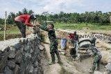 Sejumlah anggota TNI dan warga bergotong royong membangun jembatan antar Desa saat program Tentara Manunggal Membangun Desa (TMMD) di Desa Purwasedar, Ciracap, Kabupaten Sukabumi, Jawa Barat, Jumat (8/3/2019). Kodim 0622/Kabupaten Sukabumi melaksanakan program TMMD ke-104 diantaranya membangun jalan penghubung antar Desa sepanjang 5,5 km, membangun jembatan sepanjang 24 meter di atas sungai Cibangel dan pembangunan tiga gorong-gorong plat beton sepanjang 4 meter yang dilaksanakan selama 30 hari. ANTARA JABAR/Nurul Ramadhan/agr