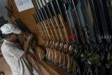 Pekerja memeriksa kondisi senapan angin yang siap dijual pada salah satu bengkel rumahan di Desa Cipacing, Kabupaten Sumedang, Jawa Barat, Kamis (14/3/2019). Produksi senapan angin di desa tersebut telah dimulai sejak tahun 1960-an yang dijual dengan kisaran harga Rp. 1 juta hingga Rp. 16 juta dan dipasarkan sampai ke mancanegara. ANTARA JABAR/Novrian Arbi/agr