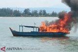 Para nelayan tradisional di Kelurahan Malabero Kota Bengkulu menahan dan membakar satu unit kapal pengguna alat tangkap pukat harimau atau trawl di tengah perairan sekitar Malabero, Kamis (14/3). Para nelayan Malabero membawa sekitar 20 kapal yang masing-masing kapal berisikan 5 hingga 15 orang anak buah kapal (ABK) berlayar menuju Pulau Baai untuk menghadang kapal trawl tersebut. (Foto Antarabengkulu.com)