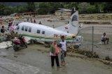 Warga berada di dekat pesawat udara yang terdampak banjir bandang di Sentani, Kabupaten Jayapura, Papua, Minggu (17/3/2019). Berdasarkan data BNPB, banjir bandang yang terjadi pada Sabtu (16/3/2019) tersebut mengakibatkan 63 orang meninggal dunia. ANTARA FOTO/Gusti Tanati/nym.