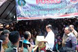 Presiden Joko Widodo (ketiga kanan) didampingi Wali Kota Sibolga M Syarfi Hutauruk (kedua kanan) menyerahkan bantuan kepada warga yang rumahnya rusak terkena dampak aksi bom bunuh diri yang dilakukan Solimah istri terduga teroris Husain alias Abu Hamzah, di Kecamatan Sibolga Sambas, Sibolga, Sumatera Utara, Minggu (17/3/2019). Presiden menyerahkan bantuan senilai Rp1.451.000.000 kepada warga yang rumahnya terkena dampak bom bunuh diri yang dilakukan Solimah pada Rabu (13/3) dini hari saat upaya penangkapan oleh Densus 88.  (Antara Sumut / Irsan )