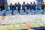 Empat petugas bersiaga di sebelah sejumlah tersangka pengedar narkoba saat dihadirkan dalam rilis ungkap kasus di Kantor BNNP Kalbar di Pontianak, Selasa (19/3/2019). BNNP Kalbar berhasil menggagalkan penyelundupan 107 kilogram sabu-sabu dan 114.669 butir dari Semenanjung Malaysia ke Kalbar melalui jalur laut di Sei Duri, Kecamatan Sungai Raya, Kabupaten Bengkayang, Kalbar pada Kamis (14/3/2019). ANTARA FOTO/HS Putra/jhw