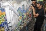Seniman Suwolo Ottobrisman (71 tahun) menyelesaikan karya seni kolase dari bahan limbah sampah plastik di Cimanggu Perikanan Darat, Kota Bogor, Jawa Barat, Selasa (19/3/2019). Seni kolase dari bahan limbah sampah plastik bekas kemasan makanan dan minuman yang telah dipamerkan ke sejumlah galeri di Indonesia hingga mancanegara seperti Spanyol dan negara Eropa Timur tersebut sebagai bagian edukasi dan mengajak masyarakat mengurangi penggunaan plastik demi menjaga lingkungan yang lebih baik. ANTARA JABAR/Arif Firmansyah/agr