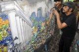 Seniman Suwolo Ottobrisman menyelesaikan karya seni kolase dari bahan limbah sampah plastik di galeri rumahnya, Cimanggu Perikanan Darat, Kelurahan Kedungwaringin, Kota Bogor, Jawa Barat, Selasa (19/3/2019). Seni kolase dari bahan limbah sampah plastik bekas kemasan makanan dan minuman yang telah dipamerkan ke sejumlah galeri di Indonesia hingga mancanegara seperti Spanyol dan negara Eropa Timur tersebut sebagai bagian edukasi dan mengajak masyarakat mengurangi penggunaan plastik demi menjaga lingkungan yang lebih baik. (ANTARA FOTO)
