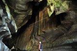 Seorang wisatawan mengunjungi gua batu kapal, di Sangir Balai Janggo, Kab.Solok Selatan, Sumatera Barat, Minggu (24/3/2019). Gua yang berada sekitar 35 kilometer dari pusat kabupaten tersebut merupakan destinasi favorit kabupaten Solok Selatan, namun akses masih terkendala jalan yang belum diaspal karena berada di kawasan kebun sawit masyarakat. (ANTARA FOTO)