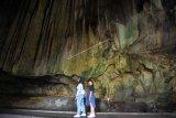 Dua wisatawan mengunjungi gua batu kapal, di Sangir Balai Janggo, Kab.Solok Selatan, Sumatera Barat, Minggu (24/3/2019). Gua yang berada sekitar 35 kilometer dari pusat kabupaten tersebut merupakan destinasi favorit kabupaten Solok Selatan, namun akses masih terkendala jalan yang belum diaspal karena berada di kawasan kebun sawit masyarakat. (ANTARA FOTO)
