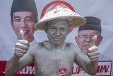 Seorang pendukung Capres - Cawapres nomor urut 01 Joko Widodo - Ma'ruf Amin berfoto saat mengikuti kampanye akbar di Stadion Singaperbangsa, Karawang, Jawa Barat, Selasa (9/4/2019). Dalam kampanye akbar tersebut Jokowi  mengajak masyarakat untuk memenangkan pasangan Capres - Cawapres nomor urut 01 dan menargetkan kemenangan sebesar 60 persen suara di Kabupaten Karawang pada Pilpres 17 April 2019 mendatang. ANTARA JABAR/M Ibnu Chazar/agr