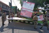 Petugas Satpol PP Kota Denpasar membongkar baliho kampanye yang masih tepasang pada hari tenang Pemilu serentak 2019 di Denpasar, Bali, Senin (15/4/2019). Kegiatan pembersihan sisa-sisa alat peraga kampanye tersebut di Denpasar akan dilakukan hingga Rabu (17/4). ANTARA FOTO/Nyoman Hendra Wibowo/nym