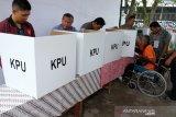 Petugas KPPS bersama pendamping mendorong kursi roda pemilih yang sakit pada pemungutan suara Pemilu 2019, di TPS 20, Helvetia Tengah, Medan, Sumatera Utara, Rabu (17/4/2019). (Antara Sumut/Irsan)