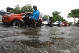 Sejumlah kendaraan bermotor melintasi banjir di ruas jalan Pangeran Antasari, Banjarmasin, Kalimantan Selatan, Sabtu (20/4/2019).Banjir yang merendam jalan Kota tersebut masih menjadi masalah rutin yang belum bisa diselesaikan Pemerintah Kota Banjarmasin saat tingginya intensitas curah hujan ditambah tata kelola drainase yang buruk dan masih rendahnya kesadaran masyarakat untuk tidak membuang sampah sembarangan. Foto Antaranews Kalsel/Bayu Pratama S.