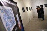 Pengunjung memindai lukisan sketsa yang di pamerkan pada lukisan digital yang bertema 'Putih di atas hitam' di Visma Art Gallery', Surabaya, Jawa Timur, Senin (22/4/2019). Pameran tersebut memadukan sketsa dengan digital yakni dengan memindai lukisan itu dengan gawai dan akan tampak konten berupa animasi dan video tentang penjelasan sketsa yang dipindai. Antara Jatim/Zabur Karuru/Zk