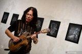 Seniman DOddy Hernanto yang akrab dipanggil Mr D bermain gitar dengan latar lukisan sketsa hasil karyanya yang di pamerkan pada lukisan digital yang bertema 'Putih di atas hitam' di Visma Art Gallery', Surabaya, Jawa Timur, Senin (22/4/2019). Pameran tersebut memadukan sketsa dengan digital yakni dengan memindai lukisan itu dengan gawai dan akan tampak konten berupa animasi dan video tentang penjelasan sketsa yang dipindai. Antara Jatim/Zabur Karuru/Zk