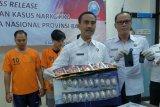 Kepala Badan Narkotika Nasional Provinsi (BNNP) Bali Brigjen Pol Putu Gede Suastawa (kedua kanan) memperlihatkan barang bukti paket narkoba dengan tersangka pengedar Made Teguh (kiri) dan rekannya Surya Adi (kedua kiri) dalam konferensi pers di kantor BNN Provinsi Bali, Bali, Senin (22/4/2019). Made Teguh yang juga sipir Lapas Kelas IIA Denpasar tersebut ditangkap bersama rekannya karena diduga sebagai jaringan pengedar narkoba yang berupaya menyelundupkan 590 ekstasi ke dalam lapas. ANTARA FOTO/Nyoman Hendra Wibowo/nym