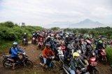 Pengendara sepeda motor melewati tanggul penahan lumpur Lapindo untuk menghindari banjir di Porong, Sidoarjo, Jawa Timur, Senin (29/4/2019). Pengendara sepeda motor tersebut tidak bisa melewati jalan raya Porong yang terendam air setinggi 60 cm akibat curah hujan yang tinggi sejak Minggu (28/4) malam. ANTARA FOTO/Umarul Faruq/nym.