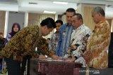 Ketua KPK Agus Rahardjo (kanan) bersama Gubernur Sumut Edy Rahmayadi (kedua kanan) Wakil Gubernur Musa Rajekshah (ketiga kanan) menyaksikan Komisaris BUMD PT Dhirga Surya Walid Musthafa Sembiring (kiri) menandatangani berkas pada Rakor Pencegahan Korupsi Terintegrasi se Provinsi Sumut, di Medan, Sumatera Utara, Selasa (14/5/2019). Rakor yang diikuti para Wali Kota dan Bupati se Sumut, direksi dan komisaris BUMD tersebut dalam rangka pencegahan korupsi di lingkungan pemerintahan daerah. (Antara Sumut/Irsan)