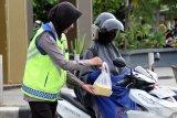 Para anggota Ditlantas Polda Kalbar membagikan takjil ke pengendara di Jalan Ahmad Yani, Pontianak, Kalimantan Barat, Kamis (16/5/2019) sore. Selain berbagi takjil, kegiatan ini juga merupakan operasi keselamatan berlalu lintas bagi pengguna jalan. ANTARA FOTO/Jessica Helena Wuysang
