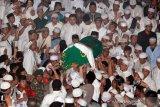 Ratusan muslim mengusung peti jenazah KH. Arifin Ilham saat akan dimakamkan di Komplek Pesantren Az Zikra Gunung Sindur, Bogor, Jawa Barat, Kamis (23/5/2019) malam. Arifin Ilham meninggal karena sakit kanker getah bening yang dideritanya. ANTARA FOTO