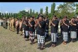 Sejumlah petugas pengamananan adat Bali atau Pecalang memberi penghormatan saat mengikuti gelar pasukan Operasi Ketupat Agung 2019 di Denpasar, Bali, Selasa (28/5/2019). Pengamanan Idul Fitri 1440 H di Bali melibatkan sebanyak 3.191 personel gabungan yang berfokus melakukan pengamanan di sejumlah potensi kerawanan seperti pengamanan jalur mudik, rumah kosong yang ditinggal mudik oleh penghuninya serta di berbagai kawasan wisata. ANTARA FOTO/Fikri Yusuf/nym