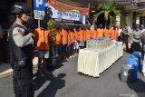 Polisi memperlihatkan barang bukti hasil Operasi Pekat Semeru 2019 di depan para tersangka di halaman Mapolresta Madiun, Jawa Timur, Selasa (28/5/2019). Selama 12 hari melaksanakan Operasi Pekat Semeru guna menjaga suasana bulan Ramadhan, Polresta Madiun mengungkap 27 kasus dan mengamankan 32 tersangka. Antara Jatim/Siswowidodo/zk