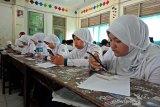 Sejumlah pelajar di MTsN 3 Meulaboh mengikuti ujian akhir semester menggunakan Handphone berbasis Android di Aceh Barat, Selasa (11/6/2019). Ujian menggunakan teknologi ini diharapkan dapat meningkatkan anak didik dalam menggunakan Handphone secara positif sekaligu meminimalisir penggunaan kertas di sekolah. (Antara Aceh/Teuku Dedi Iskandar)
