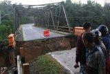 Warga melihat jembatan Ameroro yang menjadi akses jalan Trans-Sulawesi yang rusak akibat banjir bandang di Desa Ameroro, Konawe, Sulawesi Tenggara, Senin (10/6/2019). Sungai Konaweha meluap akibat banjir bandang menyebabkan akses jalan Trans-Sulawesi yang menghubungkan Sulawesi Tenggara-Sulawesi Selatan terputus. ANTARA FOTO/Jojon/nym.