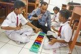Seorang guru mengajarkan berhitung siswanya menggunakan permainan congklak saat hari pertama masuk sekolah setelah libur hari raya Idul Fitri di Sekolah Luar Biasa Negeri (SLBN) Karawang, Purwasari, Karawang, Jawa Barat, Senin (17/6/2019). Sejumlah sekolah telah memulai kembali kegiatan belajar mengajar setelah libur Lebaran. ANTARA JABAR/M Ibnu Chazar/agr