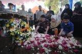 Istri dan dua anak Almarhum Kepala Pusat Data Informasi dan Humas Badan Nasional Penanggulangan Bencana (BNPB) Sutopo Purwo Nugroho, Retno Utami (tengah), Muhammad Ivanka Rizaldi Nugroho (kiri) dan Muhammad Aufa Wikantyasa Nugroho (kanan) berdoa di makam Sutopo di Tempat Pemakaman Umum Sonolayu, Boyolali, Jawa Tengah, Senin (8/7/2019). Sutopo Purwo Nugroho meninggal dunia pada usia 49 tahun karena kanker paru-paru stadium empat yang dideritanya dan dimakamkan di kampung halamannya di Boyolali, Jawa Tengah. ANTARA FOTO/Aloysius Jarot Nugroho/nym.
