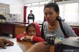 Seorang Pekerja Migran Indonesia (PMI) bersama anaknya menjalani pendataan oleh BP3TKI di Dinas Sosial Provinsi Kalbar di Pontianak, Kalimantan Barat, Rabu (10/7/2019). BP3TKI Pontianak mencatat terdapat 80 PMI yang dipulangkan Pemerintah Malaysia melalui Pos Lintas Batas Negara (PLBN) Entikong, Kabupaten Sanggau karena bermasalah dengan masa berlaku passport dan cop serta dokumen ketenagakerjaan yang tidak lengkap. ANTARA FOTO/Reza Novriandi/jhwANTARA FOTO/REZA NOVRIANDI (ANTARA FOTO/REZA NOVRIANDI)