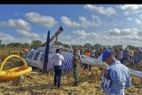 Sejumlah petugas berada di dekat pesawat helikopter B206L4 PKCDV milik PT. Carpediem Air rute Labuan Bajo-Lombok yang jatuh di luar pagar Bandara Internasional Lombok di�Desa Kawo, Kecamatan Pujut, Praya, Lombok Tengah, NTB, Minggu (14/7/2019). ANTARA FOTO/Basarnas NTB/nym.