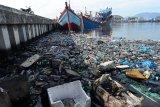 Kapal nelayan bersandar dekat tumpukan sampah botol plastik bekas bercampur minyak solar di kolam Pelabuhan Perikanan Samudera, Lampulo, Banda Aceh, Senin (15/7/2019). Pembuangan sampah botol plastik bekas dan tumpahan minyak solar tersebut mencemari kolam pelabuhan diduga berasal dari kapal nelayan dan selain kurangnya kesadaran masyarakat dalam menjaga lingkungan. (Antara Aceh/Ampelsa)