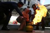 Petugas dinas pemadam kebakaran dn penyelamatan memberikan edukasi kepada warga cara memadamkan api dari tabung gas elpiji saat simulasi penanggulangan bencana kebakaran di kantor pemberdayaan perempuan dan perlindungan anak,pengendalian penduduk dnnkeluarga berencana (P3AP2KB) Kota Banda Aceh, Selasa (16/7/2019). Simulasi yang diikuti para ibu rumah tangga guna memberikan edukasi teknik pemadaman api secara manual sebagai upaya meminimalkan dampak dari bencana. (Antara Aceh/ Irwansyah Putra)
