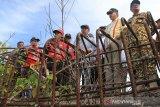 Plt Gubernur Aceh Nova Iriansyah (duakanan) meninjau jembatan penghubung Desa Tuwie Priya dan Desa Bintah yang terbengkalai di Kecamatan Pasie Raya, Aceh Jaya, Aceh, Selasa (16/7/2019). Pemerintah Aceh berencana akan melanjutan pembangunan jembatan yang terbengkalai tersebut secepatnya dan ditargetkan dapat berfungsi pada 2020 mendatang. (Antara Aceh/Syifa Yulinas)