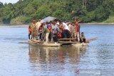 Plt Gubernur Aceh Nova Iriansyah bersama rombongan menggunakan jasa rakit penyeberangan yang menghubungkan Desa Tuwie Priya dan Desa Bintah akibat pembangunan jembatan terbengkalai di Kecamatan Pasie Raya, Aceh Jaya, Aceh, Selasa (16/7/2019). Pemerintah Aceh berencana akan melanjutkan pembangunan jembatan yang terbengkalai tersebut secepatnya dan ditargetkan dapat berfungsi pada 2020 mendatang. (Antara Aceh/Syifa Yulinnas)