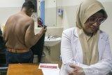 Pasien eks penderita obesitas Arya Permana (kiri) didampingi Dokter Spesialis Anak dan Gizi Anak melepas pakaian untuk  pengukuran untuk pemeriksaan awal di RSUP Hasan Sadikin, Bandung, Jawa Barat, Rabu (17/7/2019). Arya Permana yang telah berhasil menurunkan berat badan dari 190 kg menjadi 85 kg tersebut dijadwalkan akan menjalani operasi bedah plastik untuk menghilangkan gelambir atau lipatan kulit pada 24 juli mendatang. ANTARA JABAR/Novrian Arbi/agr