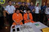 Warga negara Peru berinisial GTM (kedua kiri) dan warga Indonesia berinisial VPT (kelima kanan) yang menjadi tersangka dalam dua kasus upaya penyelundupan narkotika, dihadirkan beserta barang bukti pada konferensi pers di Kantor Pelayanan Bea Cukai Bandara Ngurah Rai, Badung, Bali, Jumat (19/7/2019). Warga negara Peru tersebut ditangkap setibanya di Bandara Ngurah Rai dengan barang bukti 950 gram kokain sedangkan VPT ditangkap sebagai penerima paket kiriman asal Jerman berupa biji tanaman ganja melalui Kantor Pos Denpasar. ANTARA FOTO/Nyoman Hendra Wibowo/nym