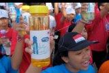 Sejumlah warga meneriakkan yel-yel dan menunjukkan botol minuman dalam kegiatan Gerakan Satu Juta Tumbler di kawasan Pantai Matahari Terbit Sanur, Denpasar, Bali, Kamis (1/8/2019). Kegiatan tersebut untuk mengajak masyarakat menggunakan botol khusus minuman sebagai pengganti botol plastik sekali pakai untuk mengurangi sampah plastik menyusul adanya temuan Komunitas Divers Clean Action bahwa 63 persen sampah di lautan Indonesia berupa sampah plastik sekali pakai. ANTARA FOTO/Nyoman Hendra Wibowo/nym.