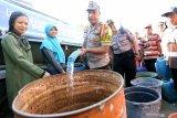 Kapolres Blitar AKBP Anisullah M Ridha (Tiga Kiri) mengisi air bersih layak konsumsi ke wadah penampungan air milik warga saat penyaluran air bersih di Dusun Nyamil, Desa Ngeni, Blitar, Jawa Timur, Sabtu (10/8/2019). Penyaluran tersebut bertujuan untuk meminimalisir dampak puncak musim kemarau yang berdasarkan prakiraan Badan Meteorologi, Klimatologi, dan Geofisika (BMKG) akan terjadi pada bulan Agustus. Antara Jatim/Irfan Anshori/zk.