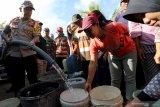 Kapolres Blitar AKBP Anisullah M Ridha mengisi air bersih layak konsumsi ke wadah penampungan air milik warga saat penyaluran air bersih di Dusun Nyamil, Desa Ngeni, Blitar, Jawa Timur, Sabtu (10/8/2019). Penyaluran tersebut bertujuan untuk meminimalisir dampak puncak musim kemarau yang berdasarkan prakiraan Badan Meteorologi, Klimatologi, dan Geofisika (BMKG) akan terjadi pada bulan Agustus. Antara Jatim/Irfan Anshori/zk.