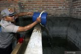 Kapolres Blitar AKBP Anisullah M Ridha mengisi air bersih layak konsumsi ke penampungan air dirumah salah seorang warga saat penyaluran air bersih di Dusun Nyamil, Desa Ngeni, Blitar, Jawa Timur, Sabtu (10/8/2019). Penyaluran tersebut bertujuan untuk meminimalisir dampak puncak musim kemarau yang berdasarkan prakiraan Badan Meteorologi, Klimatologi, dan Geofisika (BMKG) akan terjadi pada bulan Agustus. Antara Jatim/Irfan Anshori/zk.