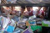 Sejumlah siswa SD memilih buku yang disediakan di mobil perpustakaan keliling saat Bursa Buku Denpasar 2019 di Denpasar, Bali, Senin (12/8/2019). Kegiatan tersebut untuk meningkatkan budaya membaca sekaligus ajang untuk mempertemukan komunitas penulis, penerbit, dan komunitas pembaca buku. ANTARA FOTO/Nyoman Hendra Wibowo/nym.