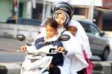 PEMKOT PONTIANAK LIBURKAN SEKOLAH. Dua anak berboncengan motor saat melintasi Jalan Ahmad Yani Pontianak, Kalimantan Barat, Selasa (13/8/2019). Pemerintah Kota Pontianak meliburkan siswa Sekolah Dasar, Taman Kanak-Kanak dan Pendidikan Anak Usia Dini (PAUD) selama dua hari yaitu Selasa (13/8) dan Rabu (14/8), menyusul semakin buruknya kondisi cuaca akibat polusi asap dari kebakaran hutan dan lahan (karhutla) yang melanda Kota Pontianak dengan Indeks Standard Pencemaran Udara (ISPU) 150 atau tidak sehat. ANTARA FOTO/Jessica Helena WuysangJESSICA HELENA WUYSANG/JESSICA HELENA WUYSANG (JESSICA HELENA WUYSANG/JESSICA HELENA WUYSANG)