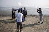Sejumlah fotografer memotret prewedding pasangan pengantin di kawasan pusat semburan lumpur Porong, Sidoarjo, Jawa Timur, Sabtu (17/8/2019). Pemerintah Kabupaten Sidoarjo mendorong pengembangan potensi wisata bahari dari endapan lumpur Lapindo yang dikenal dengan Pulau Lumpur di kawasan Tlocor, Kedungpandan, Sidoarjo. Antara Jatim/Umarul Faruq/zk